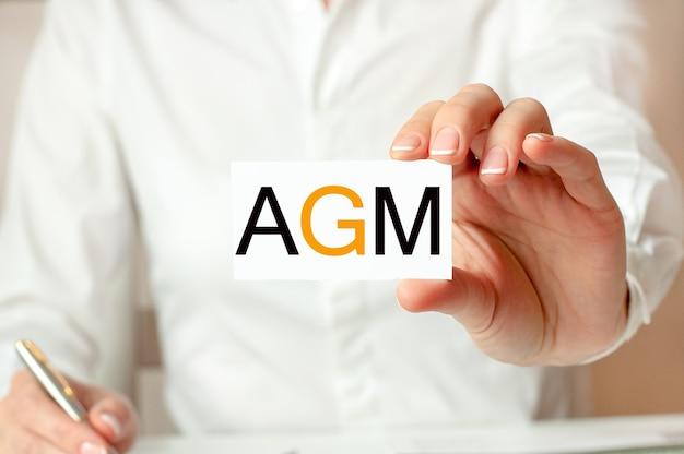 Kobieta w białej koszuli trzyma kartkę z napisem: wza. koncepcja biznesowa dla firm. agm - skrót od corocznego walnego zgromadzenia.