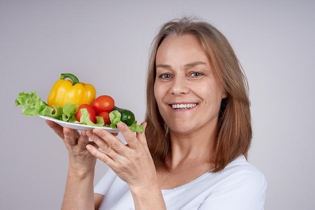 Kobieta w białej koszuli trzyma talerz z różnymi warzywami