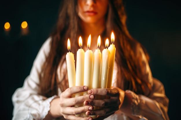 Kobieta w białej koszuli trzyma w rękach świece. rytuał czarnej magii, okultyzm i egzorcyzm, wróżby