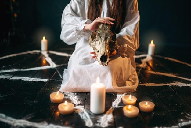 Kobieta w białej koszuli trzyma w rękach zwierzęcą czaszkę, koło pentagramu ze świecami. rytuał czarnej magii, okultyzm