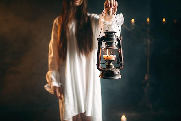 Kobieta w białej koszuli trzyma w ręku lampę naftową. rytuał czarnej magii, okultyzm i egzorcyzm