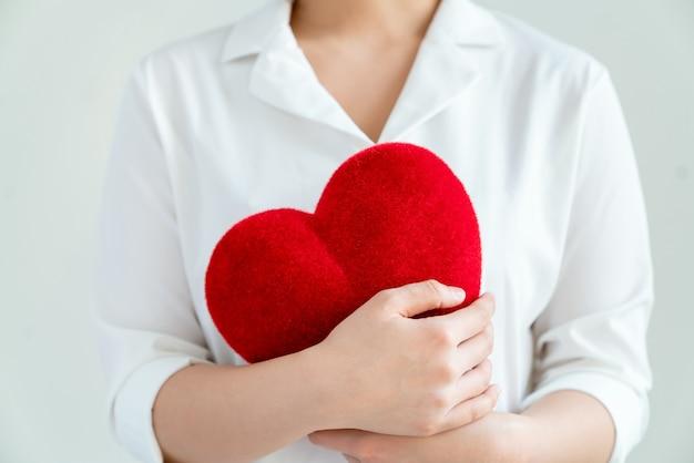 Kobieta w białej koszuli trzymając czerwone serca na szarym tle.