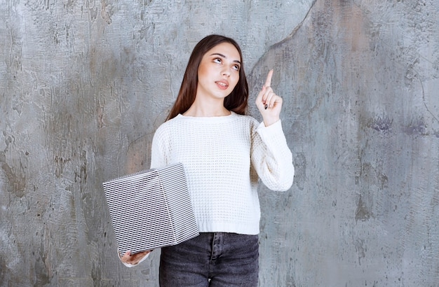 Kobieta w białej koszuli, trzymając srebrne pudełko i mając dobry pomysł.