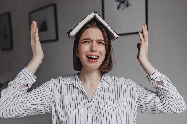 Kobieta w białej koszuli z otwartą książką na głowie płacze na tle białej ściany z nowoczesnymi obrazami.