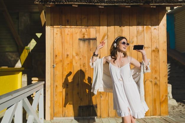 Kobieta w białej letniej sukience słuchanie muzyki na słuchawkach, taniec i zabawę