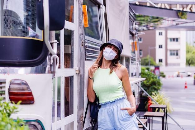 Kobieta w białej masce medycznej spaceruje po mieście przy kawiarni autobusowej na placu miejskim