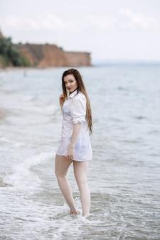Kobieta w białej odzieży orzeźwiającej nad morzem.