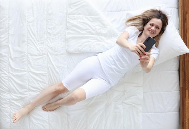 Kobieta w białej piżamie, leżąc w łóżku i biorąc selfie widok z góry. komunikacja w mediach społecznościowych