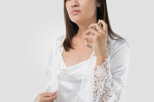 Kobieta w białej satynowej piżamie spryskuje siebie i szyję perfumami na jasnoszarym tle