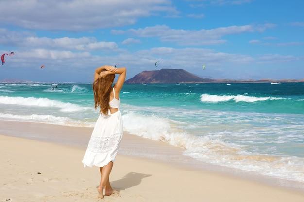 Kobieta w białej sukience spaceru na corralejo, fuerteventura