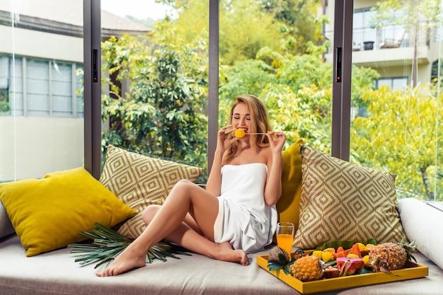 Kobieta w białej sukni balkon z widokiem na tropikalny ośrodek. owoce tropikalne. poranne śniadanie