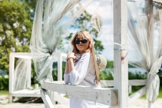 Kobieta w białej sukni cieszyć się gorący letni dzień w pobliżu piaszczystej plaży w białej drewnianej altanie. wakacje lub relaks