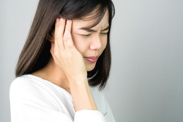 Kobieta w białej sukni dotyka głowy, aby pokazać jej ból głowy