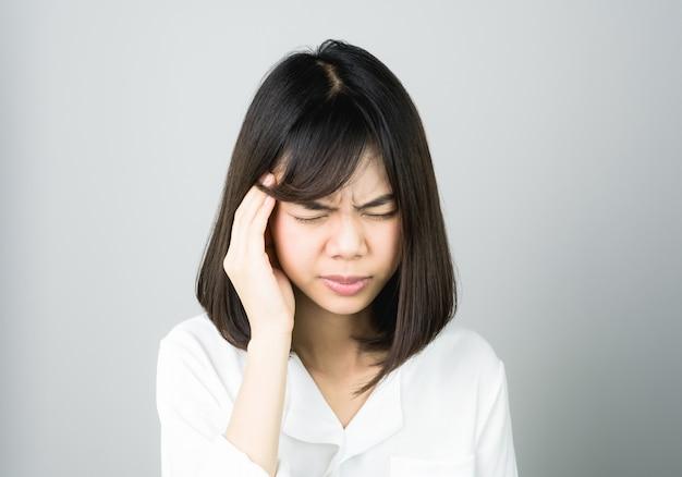 Kobieta w białej sukni dotyka głowy, aby pokazać jej ból głowy.