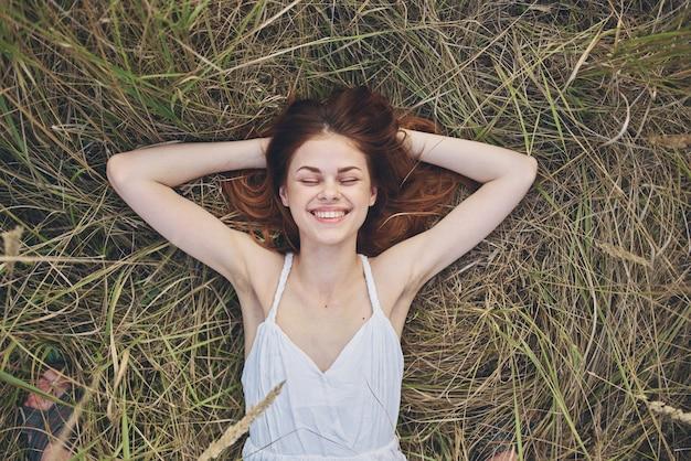Kobieta w białej sukni leży na trawie na odpoczynek natury