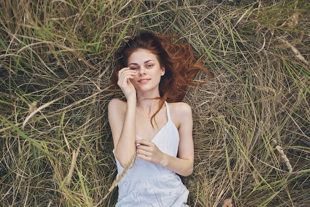 Kobieta w białej sukni leży na trawie natura relaks słońce widok z góry