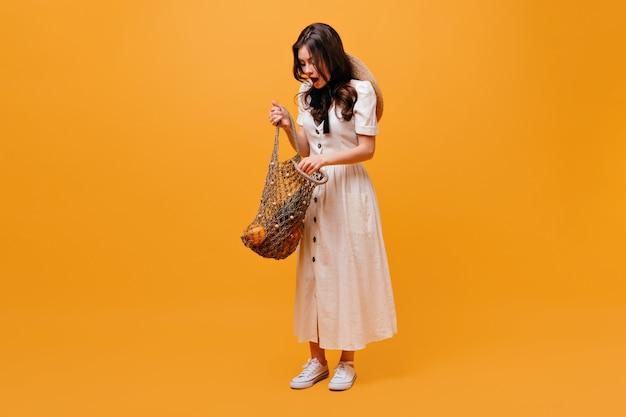 Kobieta w białej sukni otwiera torbę na zakupy z owocami i pozuje na pomarańczowym tle.