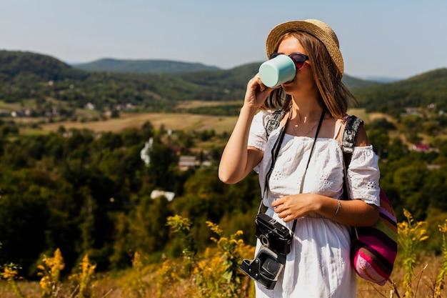 Kobieta w białej sukni picia z kubka
