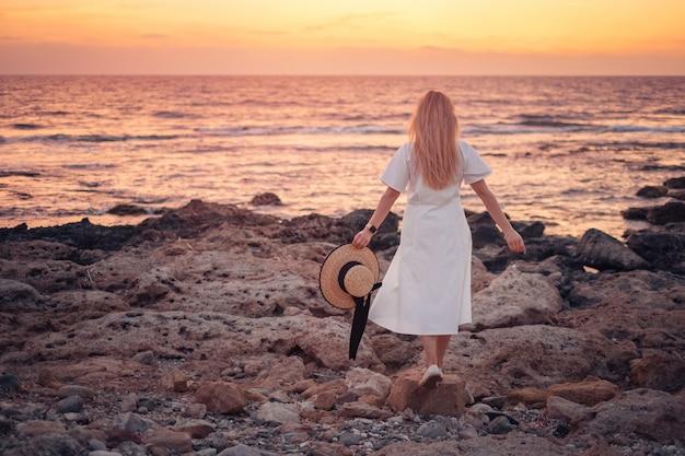 Kobieta w białej sukni, podziwiając piękny morze zachód słońca podczas podróży na cypr