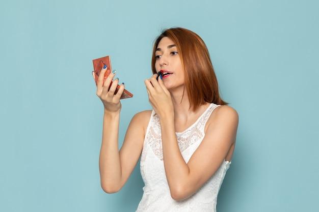 Kobieta w białej sukni, pozowanie i robi makijaż