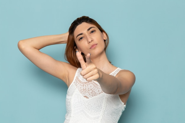 Kobieta w białej sukni pozowanie i wskazując moda pani kolor