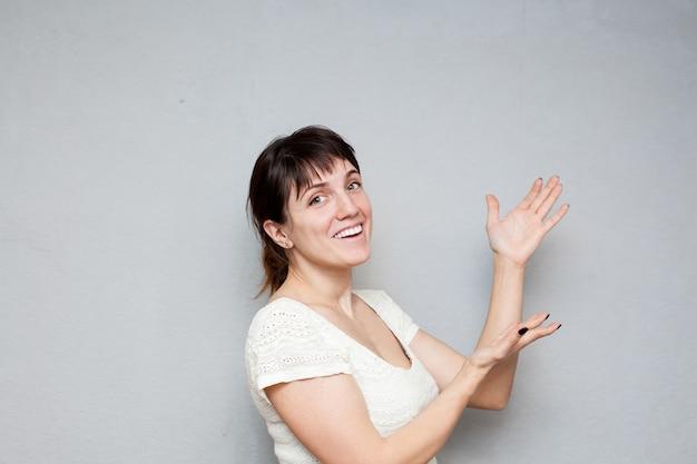 Kobieta w białej sukni, pozowanie na szarej ścianie