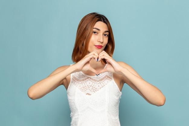 Kobieta w białej sukni pozowanie showign znak miłości