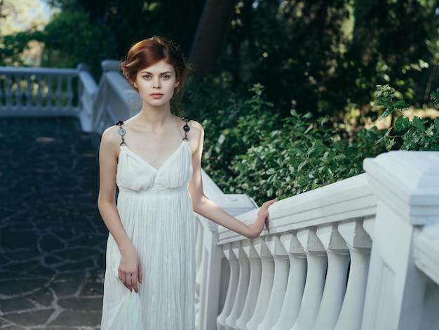 Kobieta w białej sukni pozuje parki natura lato grecja