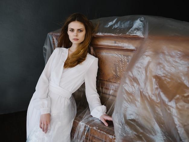 Kobieta w białej sukni pozuje w pobliżu luksusowego wnętrza instrumentu muzycznego fortepianu