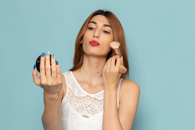 Kobieta w białej sukni robi makijaż kobieta