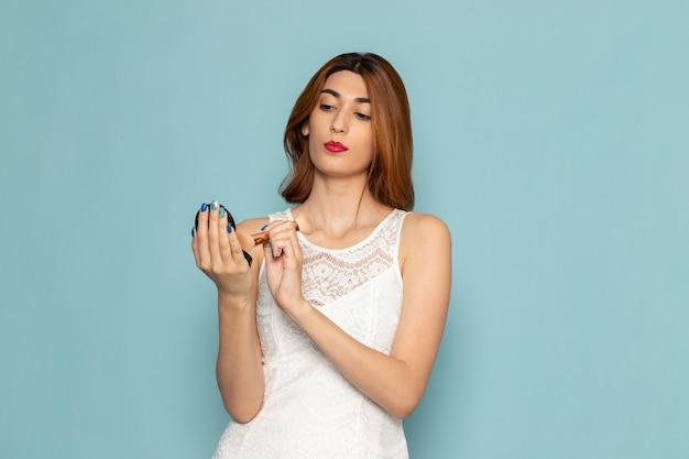 Kobieta w białej sukni robi makijaż