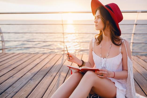 Kobieta w białej sukni siedzi nad morzem o wschodzie słońca myśli i robi notatki w dzienniku w romantycznym nastroju w czerwonym kapeluszu
