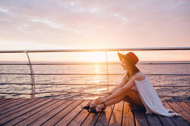 Kobieta w białej sukni siedzi nad morzem o wschodzie słońca w romantycznym nastroju na sobie czerwony kapelusz