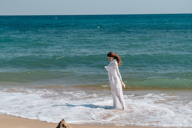 Kobieta w białej sukni stojącej na plaży