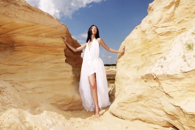 Kobieta w białej sukni tańczy na pustyni