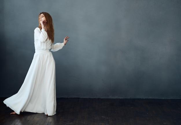 Kobieta w białej sukni taniec pozowanie występ glamour