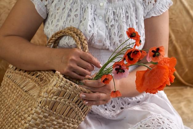 Kobieta w białej sukni trzyma kwiaty maku, z bliska na jej rękach. wiosenne sny.