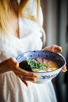 Kobieta w białej sukni trzymając azjatycką japońską zupę z makaronem shio ramen