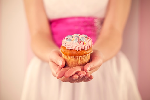 Kobieta w białej sukni trzymając różową babeczkę