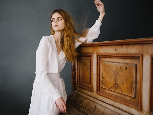 Kobieta w białej sukni urok pozuje wnętrze fortepianu