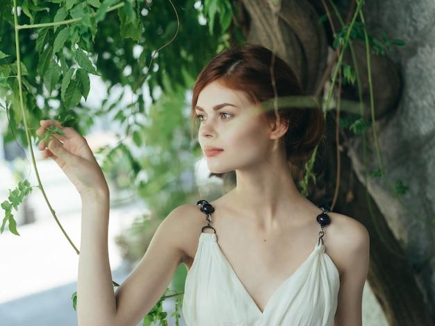 Kobieta w białej sukni w pobliżu drzewa kamienna ściana ozdoba stylu życia