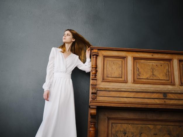 Kobieta w białej sukni w pobliżu fortepianowego uroku wnętrza i luksusowej mody pozowania