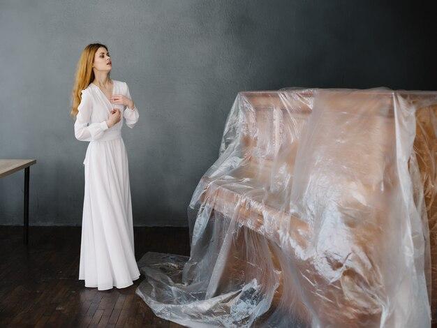 Kobieta w białej sukni w pobliżu przykutego romansu fortepianowego