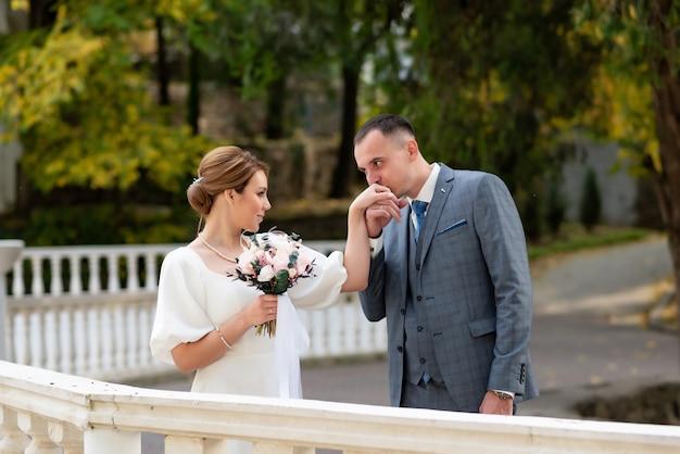 Kobieta w białej sukni z bukietem ślubnym wraz z panem młodym po ceremonii ślubnej