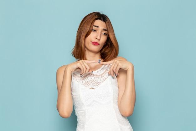 Kobieta w białej sukni z niezadowolonym wyrazem twarzy