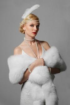 Kobieta w białej sukni z pasami na ramię i długą futerkową stułą