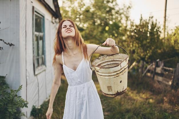 Kobieta w białej sukni z wiaderkami w ręku natura styl życia. zdjęcie wysokiej jakości