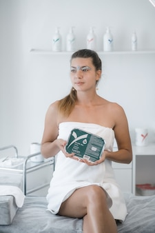 Kobieta w białej szacie z woskiem na brwiach w salonie kosmetycznym