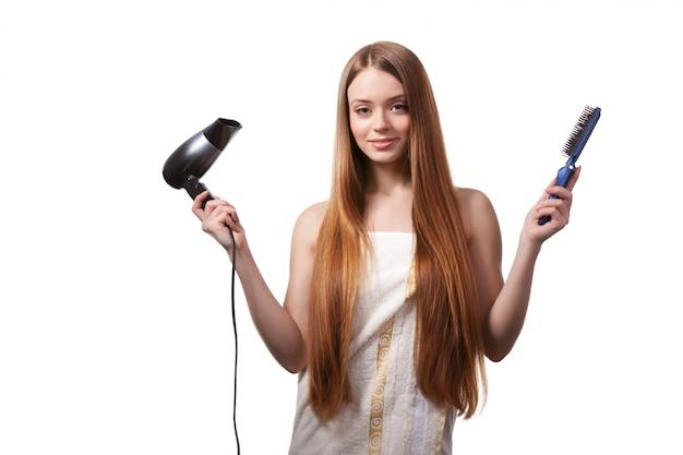 Kobieta w biały ręcznik suszenia włosów z suszarką do włosów