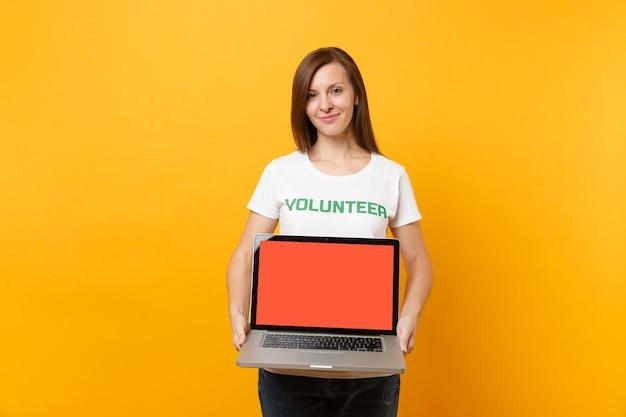 Kobieta w biały t-shirt napisany napis zielony tytuł wolontariusz trzymać komputer przenośny pc, pusty pusty ekran na białym tle na żółtym tle. dobrowolna bezpłatna pomoc pomoc, koncepcja pracy łaski charytatywnej.